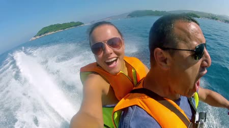 esqui : Jetski waverunners selfie of father and daughter having fun fast riding a motor boat, HD stock video