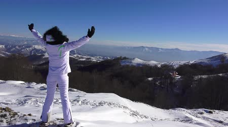 aventura : 4k Hands raised Girl on the snow mountain top. Freedom concept. uhd steadycam stock video Vídeos