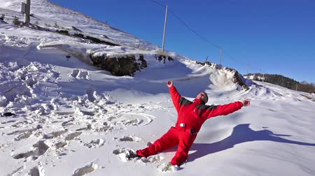 snow angel : SLOW MOTION: Young man falling and making snow angels, steadycam stock video Stock Footage