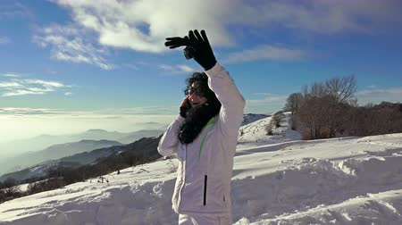 falar : 4K Smartphone woman talking on phone laughing on snow. Beautiful hispanic young female professional having conversation on mobile phone. UHD steadycam stock video