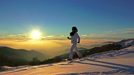 quad hd : 4k runner girl running downhill exercise. winter snow sunset mountain top,  recreation activity outdoors sports, UHD steadycam stock video Stock Footage