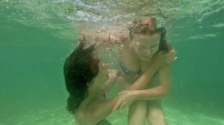 underwater video : Beauty young woman swimming and having fun diving underwater at sea laguna. Drowning game play. Slow motion video footage HD 1080p Stock Footage