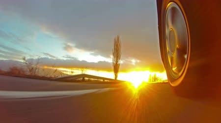 saturado : 4k Driving a sport car on a country road at sunset. Wheel spinning POV - Point of View. UHD Fast Speed  time-lapse.