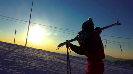 esqui : 4K Silhouette of a woman with ski in winter mountains sunset close up. UHD steadycam stock video