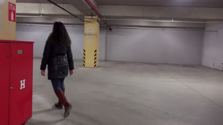 repce : 4K Robber follow fashion girl walking in underground mall car parking lot. UHD steadycam stock video