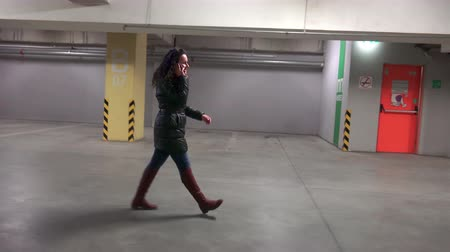repce : 4K robber following fashion shopping girl walking and talking to phone in underground mall car parking lot. UHD steadycam stock video, side view