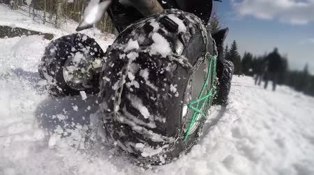sporty zimowe : ATV riders on winter snow racing. Super slow motion of snow fly toward camera