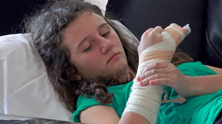 sıva : 4k Girl with broken hand and cast on it lying in hospital bed. Close up on plaster, cast, gypsum. UHD stock video