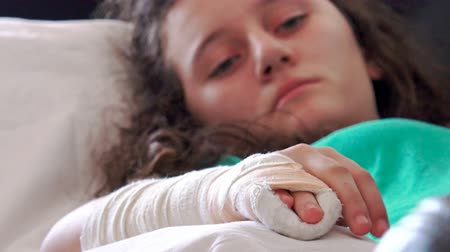 elenco : 4k Girl with broken hand and cast on it lying in hospital bed. Close up on plaster, cast, gypsum. UHD stock video
