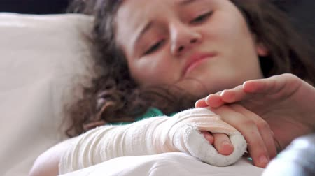 elenco : 4k Girl masage her broken hand with cast on it. Lying in hospital bed. Close up on plaster, cast, gypsum. UHD stock video