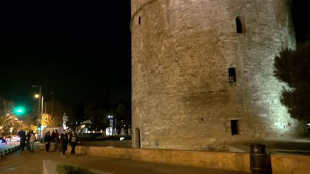 zár : Trafic jam at White Tower of Thessaloniki at night, Greece. UHD stock footage Stock mozgókép