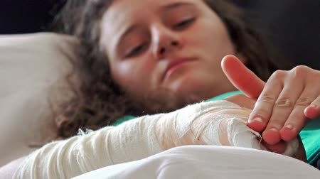 elenco : 4k Girl pain from broken hand and cast on it lying in hospital bed. UHD stock video