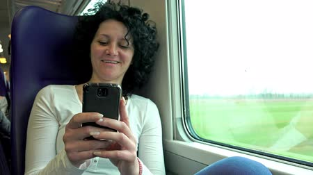 метро : 4k Young Happy Woman Texting with Cell phone While Traveling by Train. UHD stock footage Стоковые видеозаписи