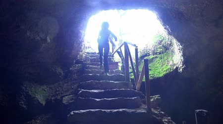 barlang : Girl escape giant cave walking the stairs . UHD 4K steadycam stock footage Stock mozgókép