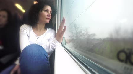 okno : Woman looks out of window on train trip during movement. 4k uhd stock footage Wideo