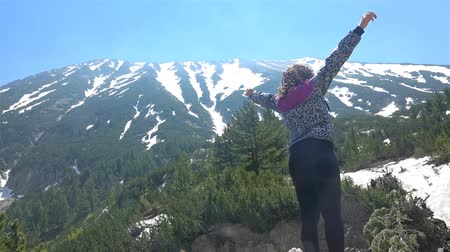 picos : Young girl hiker do victory pose with hands open near mountain peak with snow melting waters spring flow. UHD 4K steadycam stock footage Vídeos