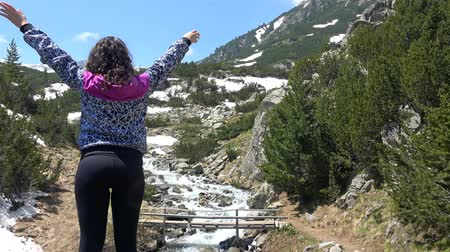 wspinaczka górska : Young girl hiker do victory pose with hands open near mountain peak with snow melting waters spring flow. UHD 4K steadycam stock footage Wideo