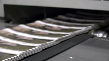 print shop : Newspapers flow along an assembly line in a newspaper print factory. UHD 4K stock footage