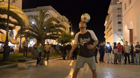 gösterileri : Fantastic ball performance on street at night. Soccer player makes a soccer freestyle demonstration in front of audience. 4k UHD steadycam stock footage Stok Video