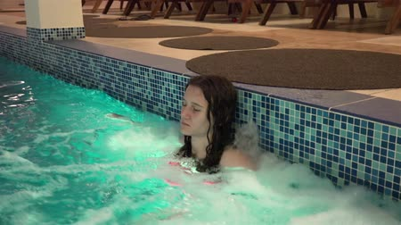 hidromassagem : Young girl enjoy jacuzzi side of the pool, smiling and looking in camera. UHD 4K steadycam stock footage