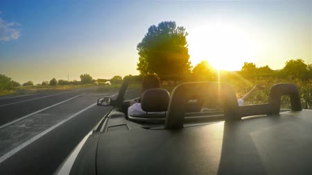 kabriolet : Romantic couple in convertable cabriolet car turn off the highway with sunset sun ray shining. UHD 4K stock footage
