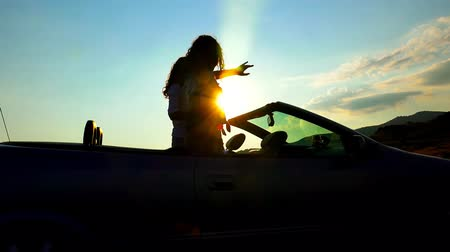крейсерский : Close up of party couple with hands up, driving convertible, cabriolet car, at sunset with sun flare. Steadicam shot. UHD 4K stock footage
