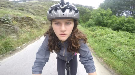 quad bike : Girl Cycling - A girl with cycle helmet cycling on rural road in a park. camera attached to helmet pov Stock Footage
