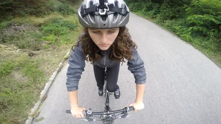 bisiklete binme : Girl Cycling - A girl with cycle helmet cycling on rural road in a park, view from top front. camera attached to helmet pov
