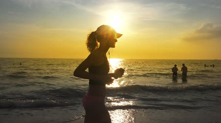 outdoor : Young woman with a slender figure and hat is engaged in gymnastics at sea at sunrise. She makes a run along the sea coast. Steadycam camera stabilizer shots. Stock Footage