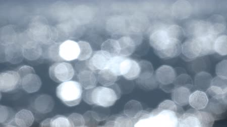 season : Bokeh from Sparkling fresh wavy water is shining on a sunny summer day, abstract blurry uhd background at the seaside Stock Footage