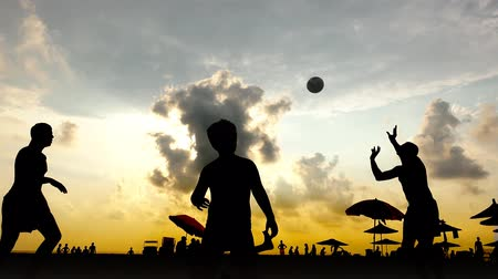 röplabda : Young people playing volleyball on the summer beach at sunset. uhd footage Stock mozgókép