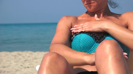 půvabný : Sexy girl using sun block skin cream protection on chest and sunbathing on beach, closeup