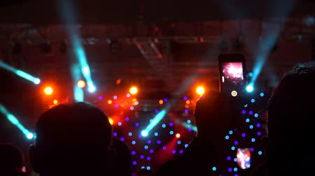 fényszóró : 4k Back view of people standing in stage lights and recording with smartphone Stock mozgókép
