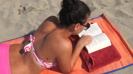 banhos de sol : 4k Young women reading a book lying at the beach sand with waves and horizon in the background, closeup Vídeos