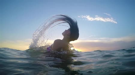 sunrice : Woman makes spiral splashing water with her hair at sea sunset surface. SLOW MOTION HD