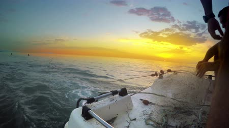 fishing industry : Fisherman throwing his fishing net from boat at sea sunset