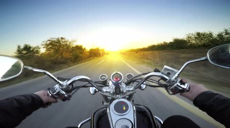 motocykl : A motorcycle road adventure going forward to the sun in high speed. pov at sunset.