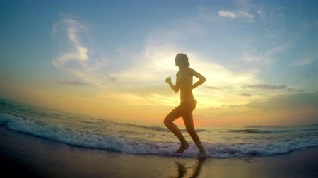 jogging : Girl model running jogging barefoot  at beach sunset Stock Footage