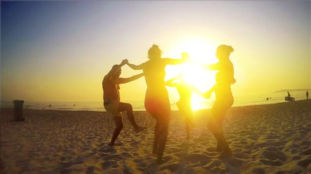 четыре человека : Four people dancing over sun on the beach, SLOW MOTIION