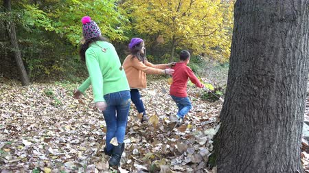 Three kids running in forest throwing autumn leaves