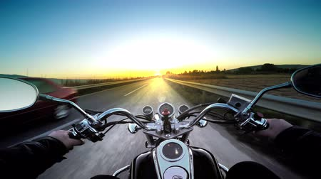 Driving motorbike on asphalt road toward heavenly sunset. POV