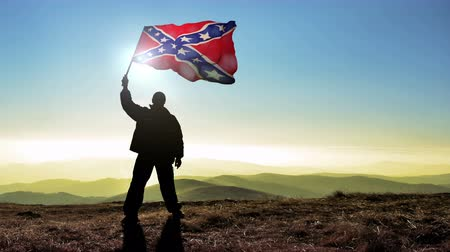 diadal : Successful silhouette man winner waving Confederate flag on top of the mountain peak, 4k cinemagraph