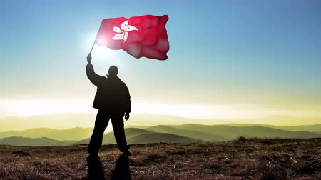 conquest : Successful silhouette man winner waving Hong Kong flag on top of the mountain peak, 4k cinemagraph Stock Footage