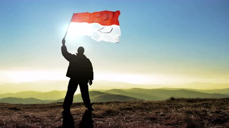 conquest : Successful silhouette man winner waving Indonesia flag on top of the mountain peak, 4k cinemagraph