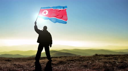 conquest : Successful silhouette man winner waving North Korea flag on top of the mountain peak, 4k cinemagraph Stock Footage