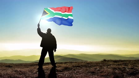 délre : Successful silhouette man winner waving South Africa flag on top of the mountain peak, 4k cinemagraph Stock mozgókép