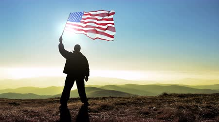 keşif : Successful silhouette man winner waving USA United States of America flag on top of the mountain peak, 4k cinemagraph