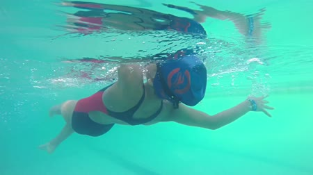 profi : Female swimmer in rubber cap training back swimming in swimming pool, underwater view, SLOW MOTION