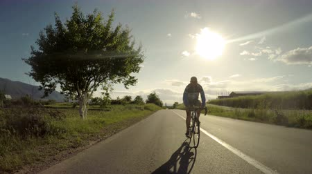 sunrice : healthy man riding bicycle working out fitness outdoors at the sunset. tracking shot 4k from camera car Stock Footage
