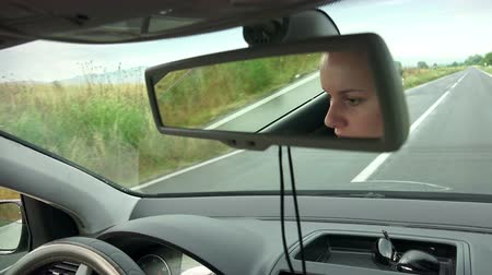 камедь : beautiful young woman in her car driving on a country road and chewing bubble gum Стоковые видеозаписи